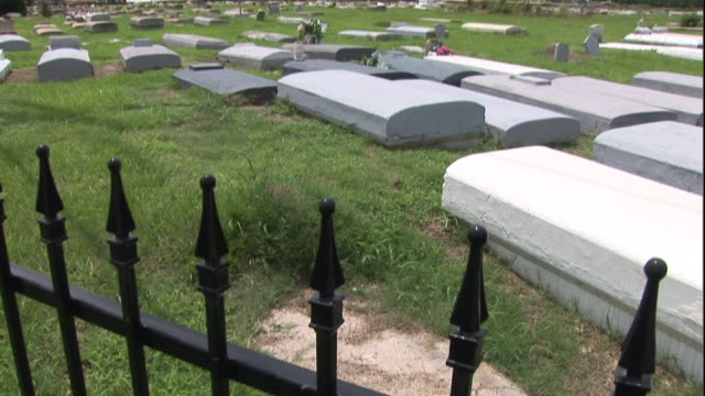 an iron fence surrounds a large cemetery. - cemetery stock videos & royalty-free footage