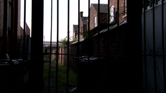 an iron gate encloses a yard and row houses. available in hd. - villetta a schiera casa video stock e b–roll