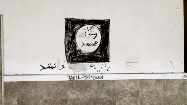 vídeos y material grabado en eventos de stock de an islamic state flag painted on the wall of a church in the predominantly christian village of bartella during the occupation by isis is seen after... - isis