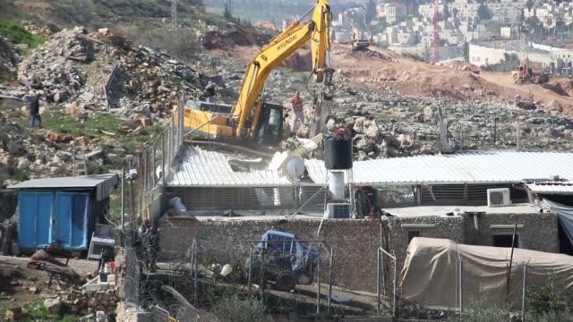 an israeli bulldozer demolishes a palestinian house in the east jerusalem neighborhood of shuafat on february 21 2018 - east jerusalem stock videos and b-roll footage