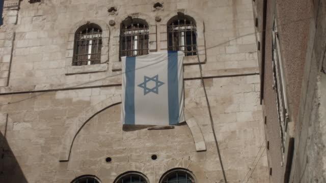 an israeli flag hangs outside of a ancient window in jerusalem's old city on november 25, 2014 in jerusalem, israel. nine israelis have been killed... - old town stock videos & royalty-free footage