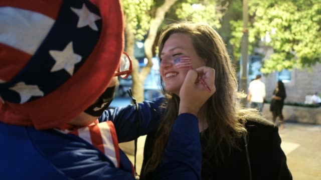 july 04: an israeli man dressed in uncle sam outfit paints the american flag on a woman`s face during united states fourth of july independence day... - fourth of july stock videos & royalty-free footage