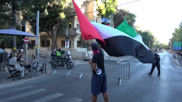 an israeli man walks with a large flag of the united arab emirates in gaza street on august 20, 2020 in jerusalem, israel. israel and the united arab... - ガザ地区点の映像素材/bロール
