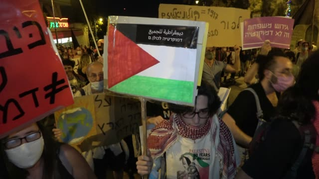 an israeli protester holds up a placard painted with the colors of the palestinian flag during a mass demonstration attended by over 15000 people as... - palestinian flag stock videos & royalty-free footage