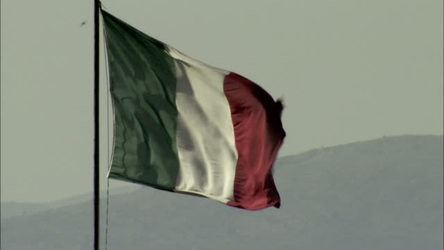 an italian flag waves in the breeze in front of mountains. available in hd. - italian culture stock videos & royalty-free footage