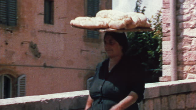 an italian woman carries loaves of bread on her head as she walks through the streets of umbria, italy, while another woman hands bread, wine and eggs up to a third floor window by way of a pulley. - ウンブリア州点の映像素材/bロール