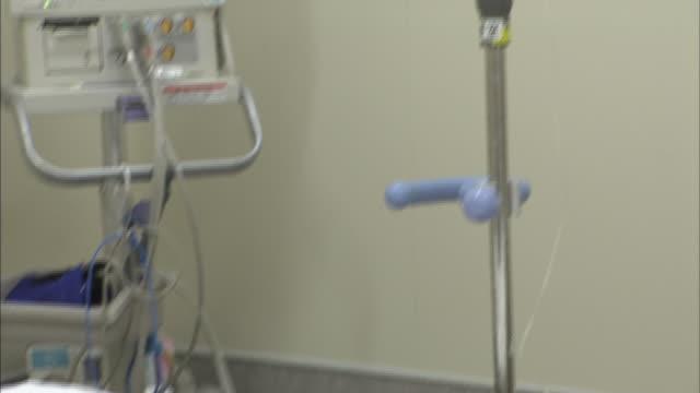 vidéos et rushes de an iv drip hangs from a pole next to an empty hospital bed. - rétablissement