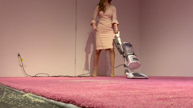 an ivanka trump lookalike model vacuums bread crumbs thrown by visitors as part of an art installation titled ivanka vacuuming at the flashpoint... - doppelgänger stock-videos und b-roll-filmmaterial