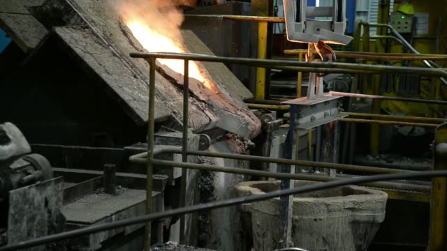 stockvideo's en b-roll-footage met an ixl worker pours a sand composite into a mold in the foundry at ixl industries residue is burnt off a mold preparing it for re use in the foundry... - soeplepel