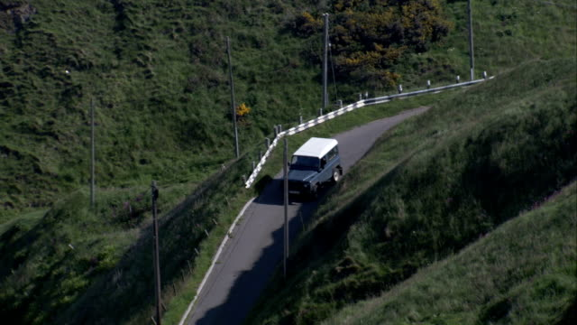 an jeep travels down a hillside road to reach the village of crovie scotland. available in hd. - クロヴィー点の映像素材/bロール