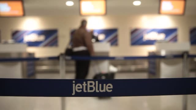 an jet blue employee assists a traveler at the checkin counter at ronald reagan national airport in washington dc us on thursday jan 23 various jet... - ronald reagan washington national airport stock videos and b-roll footage