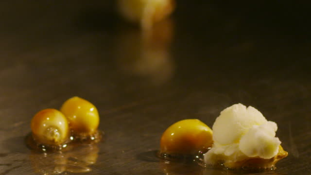 an ecu of kernels popping in oil over a hot griddle. - popcorn stock-videos und b-roll-filmmaterial