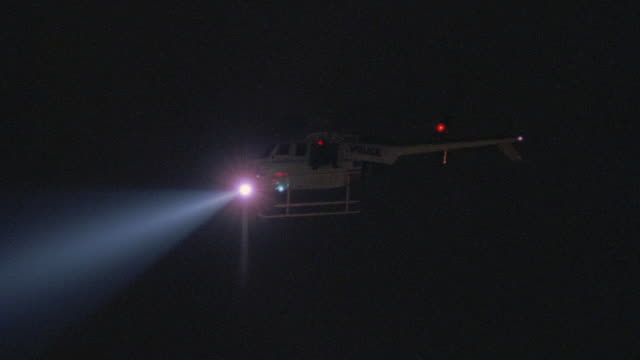 an lapd police helicopter beaming a searchlight in hollywood at night. - los angeles police department stock videos & royalty-free footage