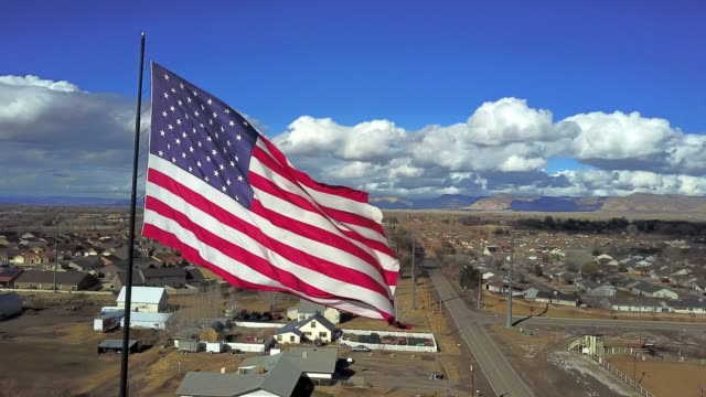 vídeos de stock e filmes b-roll de an large american flag flying on a beautiful fall day - patriotismo