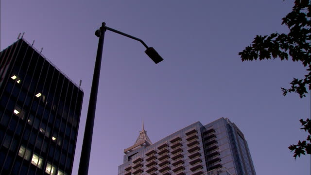 an led street lamp turns on as darkness falls. - an oder ausschalten stock-videos und b-roll-filmmaterial