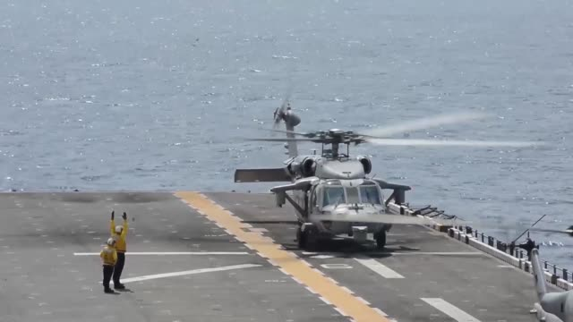 An MH60S Knighthawk helicopter assigned to Helicopter Sea Combat Squadron 25 performs flight operations out of the forwarddeployed amphibious assault...