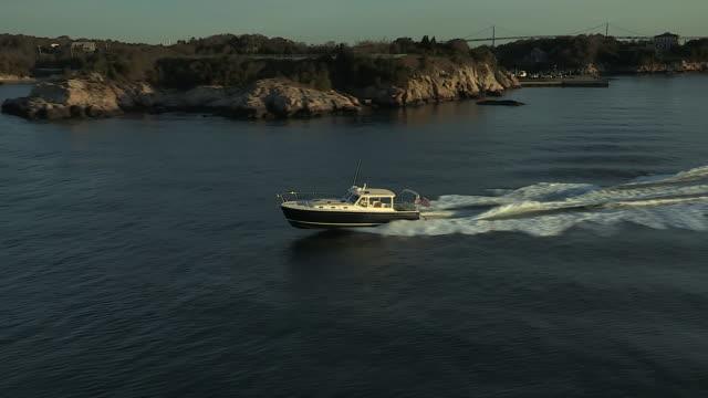 an mjm 40z powerboat  speeds along narragansett bay along the jamestown shoreline. - jamestown stock-videos und b-roll-filmmaterial