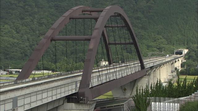 vidéos et rushes de an mlx01901a ultra longnose linear motor car speeds across a rail bridge during its experimental stage - préfecture de yamanashi