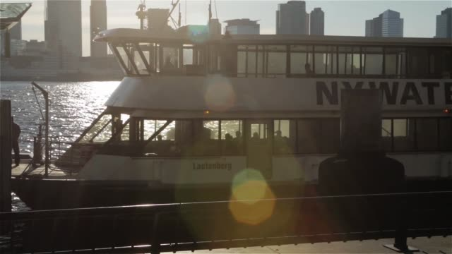 an ny waterway water taxi sits docked at a station in nelson rockefeller park in downtown manhattan new york new york on june 24th 2015 shots wide... - zurücklehnen stock-videos und b-roll-filmmaterial