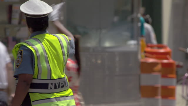 an nydp police officer directs traffic on a hot summer day in new york city.   - trillerpfeife stock-videos und b-roll-filmmaterial