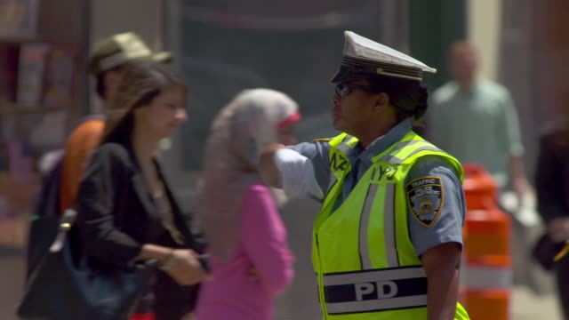 an nydp police officer directs traffic on a hot summer day in new york city.   - 警察点の映像素材/bロール