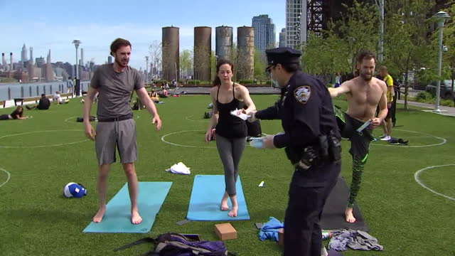 an nypd officer passes out masks to people exercising at domino park in brooklyn during the coronavirus pandemic. - healthcare and medicine or illness or food and drink or fitness or exercise or wellbeing stock videos & royalty-free footage