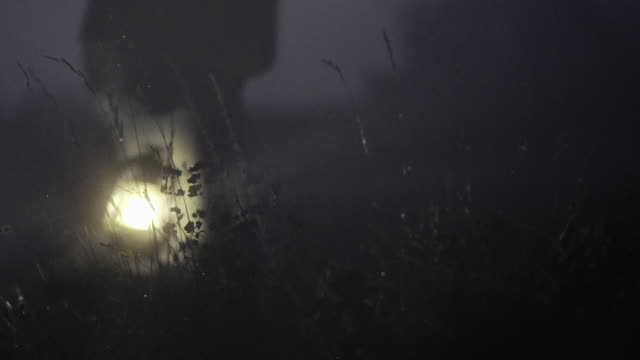 an obscured man walks through a field at night - lantern stock videos & royalty-free footage
