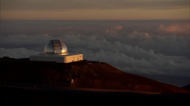 vídeos de stock, filmes e b-roll de an observatory on the summit of mauna kea overlooks a cloud-covered pacific ocean. - espaço e astronomia