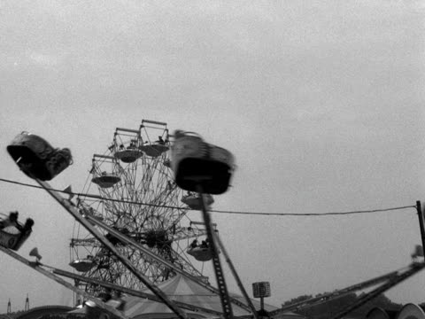 stockvideo's en b-roll-footage met an octopus ride spins passengers around at a funfair whilst a big wheel in the background stops to allow passengers on and off the ride 1959 - ongewerveld dier