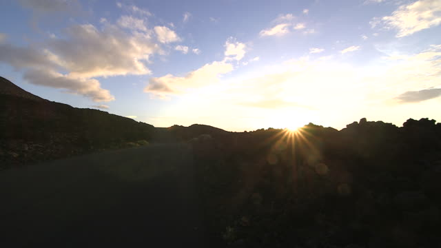 vídeos de stock, filmes e b-roll de an off road vehicle travels along a coastal road on the island of el hierro. - hierro