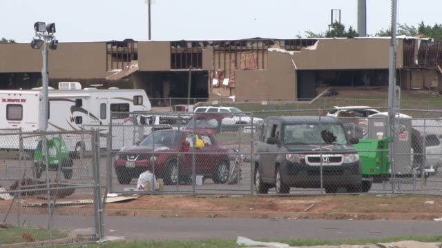 an office building, along with vehicles in the parking lot are completely destroyed in the aftermath of the moore, oklahoma tornado of may 20th, 2013. - 2013 stock videos & royalty-free footage