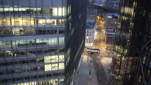 An office building and city streets at dusk.