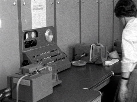 an office worker checks a meteorological machine at the met offices new office in berkshire. 1961. - meteorology stock videos & royalty-free footage