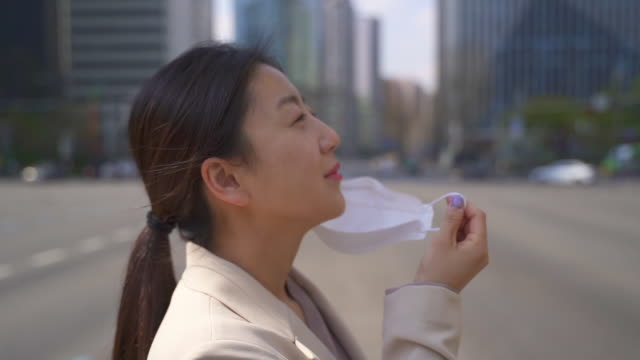 an office worker on the way to workplace smiling while taking off a protective mask to prevent covid-19 / seoul, south korea - removing stock videos & royalty-free footage