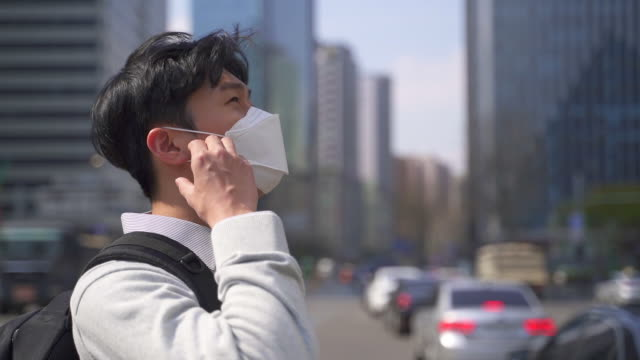 an office worker on the way to workplace smiling while taking off a protective mask to prevent covid-19 / seoul, south korea - absence点の映像素材/bロール