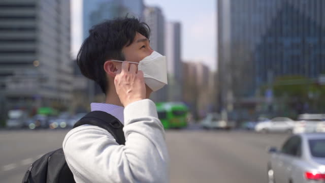 vídeos de stock, filmes e b-roll de an office worker on the way to workplace smiling while taking off a protective mask to prevent covid-19 / seoul, south korea - despindo se
