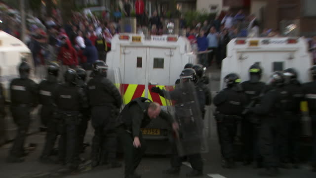 an officer forming part of a blockade in a police effort to prevent sectarian violence is struck by a heavy flying object, falls to the ground, and is dragged away by other officers, july 2015, belfast, northern ireland. - ufficiale grado delle forze armate video stock e b–roll