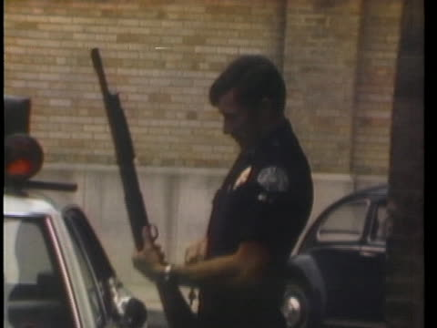 an officer loads his rifle in front of a los angeles precinct after a questionable chemical fire. - city of los angeles stock videos & royalty-free footage