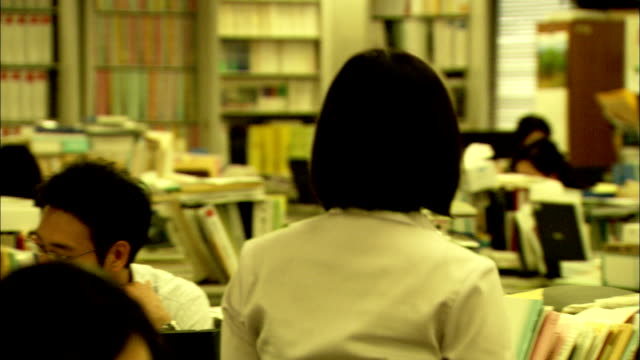 An office-worker takes a file from a desk, Japan. Available in HD.