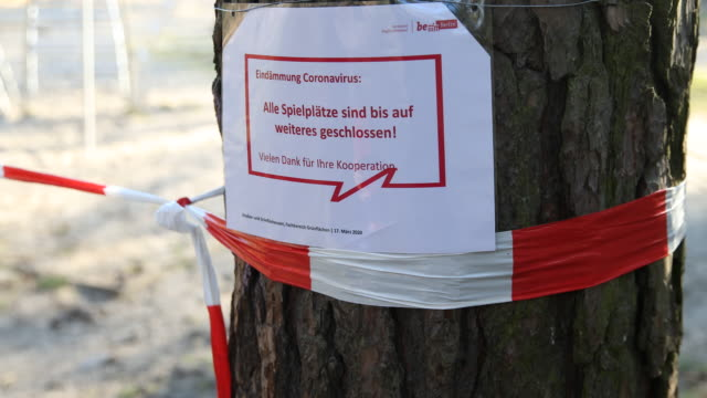 an official sign with the inscription that all playgrounds in berlin are concluded for an indefinite period following a city ordinance temporarily... - geschäftliche aktivitäten stock-videos und b-roll-filmmaterial