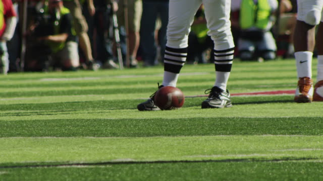 An official stands next to a football at the line of scrimmage, as players approach.