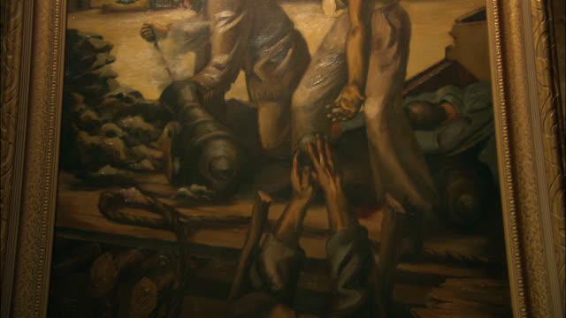 vídeos de stock e filmes b-roll de an oil painting in the alamo depicts a man loading a cannon. - museu