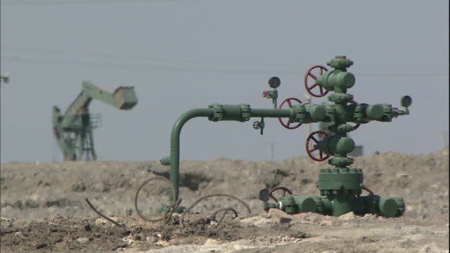 An oil pump jack moves up and down near an excavating machine in an oilfield.