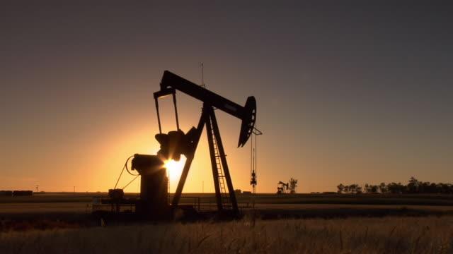 vidéos et rushes de an oil pump pumps slowly in a north dakota field. - dakota du nord