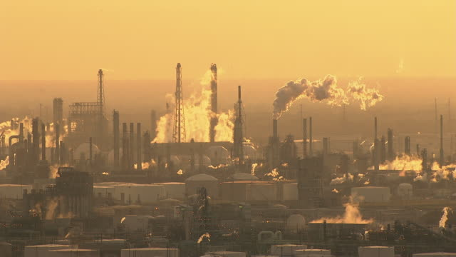 an oil refinery puffs smoke in houston, texas. - gulf coast states stock-videos und b-roll-filmmaterial