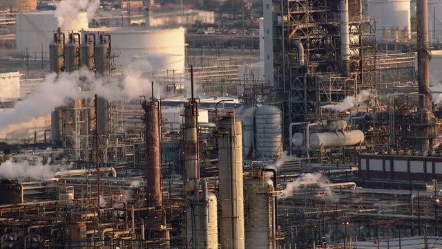 an oil refinery spews smoke in houston, texas. - fabriksskorsten bildbanksvideor och videomaterial från bakom kulisserna