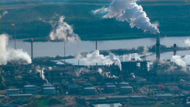 An oil refinery's smokestacks emit smoke.