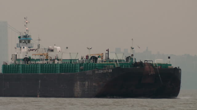 vídeos y material grabado en eventos de stock de an oil tanker barge heads down the hudson river, the george washington bridge is behind - barcaza embarcación industrial