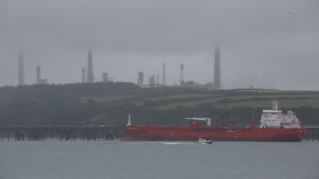 an oil tanker offloading at a refinery at milford haven, pembrokeshire, wales, uk. - storage tank stock videos & royalty-free footage
