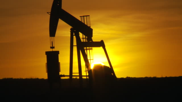 An oil well jack pumps oil in North Dakota during the golden hour.